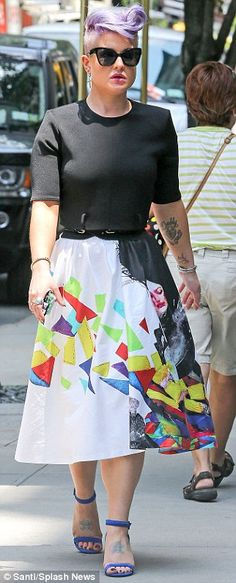 Style chameleon: Kelly chose a black cropped top and another white midi-skirt for her second round of press, though this one featured a black a white image of a woman on the side and a multi-coloured design splashed across the rest