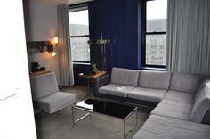 This could work for the new place: gray leather couch, blue accent wall and a comfy chair