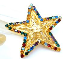 Sparkly Vintage Costume Jewelry - This is a gold tone star with prong set multi colored rhinestones and an open work floral design. This pin measures 2.25 inch in diameter and is in great condition.