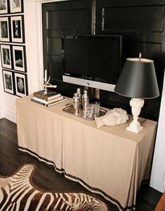 hide tv wires and components with a skirted table. I hate the glass console my husband bought before we were married. time to hide it!