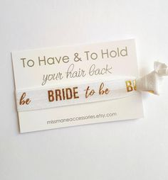 """Bride to be Hair Tie Bracelets are the perfect gift to give to the bride to be! Each band comes on a white card with gold metallic font.  ♥A girl can never have enough hair ties--and they will adore these """"BRIDE"""" hair tie favours---great for any hen party/bachelorette event or add on to their big gift or hand them out to your wedding guests!  ♥You always seem to need a hair tie when you don't have one and these are cute enough to wear on your wrist until you do. Hair Tie Bracelet, Bracelets, Big Gift, Bachelorette Favors, Bridal Salon, Bride Hairstyles, Bride Gifts, Favours, Hair Ties"""