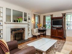 Traditional Living Room with Built in shelves, brick fireplace, Stained vintage coffee table, Hardwood flooring, Hung window
