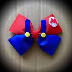 Super Mario Character Inspired Blue Mario Cartoon Hair Bow Blue & Red Grosgrain Ribbon Decorated with Felt Accents. Mounted on an alligator clip. I can do custom bows, just let me know if youd like something specific. Price is for single bow. Hair Ribbons, Ribbon Bows, Grosgrain Ribbon, Disney Hair Bows, Cartoon Hair, Custom Bows, Felt Bows, Diy Hair Accessories, Bridal Accessories
