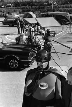 Adam West tries out his Bat-communicator while the crew sets up a shot with the Batmobile.