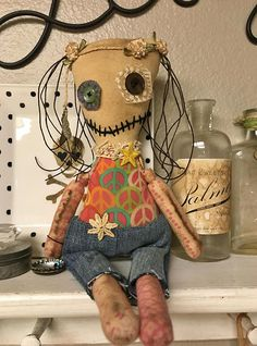 OOAK hippie monster doll Doobie is approximately 13 inches tall. She is made of new and used fabric and yarn. Her body is made of coffee stained muslin. She has feathers in her hair, a button on her behind, and carries a bottle cap that reads, Be your own orchestra. *** Because of