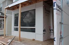 Front of house with canopy and wing wall under construction.
