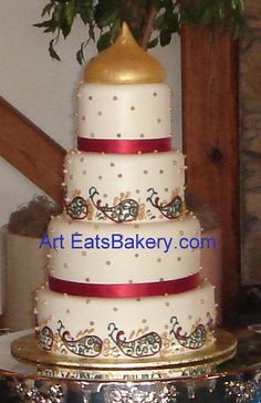 Four tier ivory fondant wedding cake with varied gold, and copper sugar pearls, red, teal and gold Mehndi design