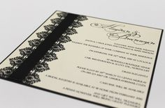 A flat invitation printed on ivory shimmer layered on a black backing card with a printed decorative detail with a ribbon to add another textural dimension.