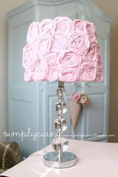 DIY shabby chic lampshade: page is not found, but you can still do this!  Twirl fabric strips into a pinwheel, placing dots of glue every so often. Varying lengths of fabric determine size of roses. Glue roses to lampshade to finish :) She did an awesome job on this!