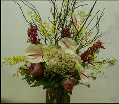 A lush display featuring yellow oncidium orchids, white anthurium and protea.  To view our entire selection, please visit us at www.starflor.com #flowers #eventdecor #events