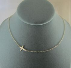 Sideways Gold Cross Necklace Off Center by shix on Etsy, $26.00  I like things a bit different and this fits the bill!