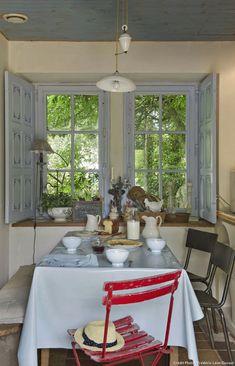 Au-dessus de la table dressée pour un petit déjeuner sur toile cirée, un monte-et-baisse avec son poids en porcelaine. Aux douces tonalités grises et bleues répond le vert éclatant des arbres du jardin.