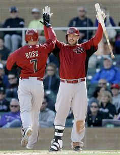 Arizona Diamondbacks' Eric Hinske, right, greets Cody Ross (7) at the plate after Ross scored on a triple from Eric Chavez during the fifth inning of an exhibition spring training baseball game against the Colorado Rockies, Sunday, Feb. 24, 2013, in Scottsdale, Ariz. (AP Photo/Marcio Jose Sanchez)