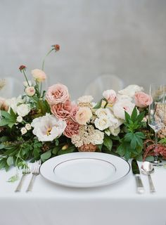 Peonies, carnations, roses, and ranunculus lay across the wedding table: http://www.stylemepretty.com/2016/12/06/how-to-rock-a-bridal-cape/ Photography: Almond Leaf Studios - http://almondleafstudios.com/