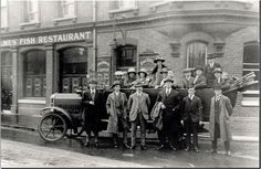 Kings Road, Reading. South side, No. 172, Holmes' Fish Restaurant, at the corner of Kennet Street, c. 1923. Outside the restaurant, members of the Duce family, who owned it, pose on and by a char-a-banc, which is waiting to take them on an outing. 1920-1929 : copy of an older photograph. Reading Borough Libraries