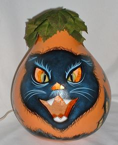 My hand painted light up Black Cat Jack-O-Lantern is 11 tall and 29 around. He is my new design for this Halloween. He has haunted houses all