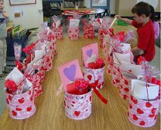 Valentine cans = Acrylic paint in pink, red, or white.  Sponge paint heart shapes.  Attach a handle and add a fabric or raffia bow.  CUTE!