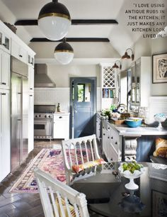 It's an old kitchen re-done, but I love how they did awkward and made it fresh and usable.  Like the blue door and pop of color in the rug