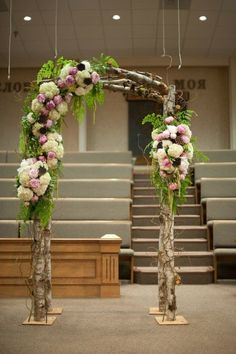 rough tree branches arch with lush florals and greenery