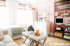 This feminine studio is the perfect example of why small-space dwellers should invest in double-duty furniture. A pair of upholstered ottomans act as a coffee table, but also function as additional seating. A tall bookcase emphasizes the room's height while also offering storage space and a place to prop the television.