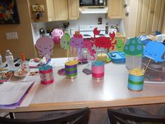 Under the sea centerpieces. All you need is a few large pineapple tin cans. double sided tape and your favorite ribbon. To create the diecuts you'll need a Cricut machine and the cartridge used is I believe Little Creatures. I then double sided taped the diecuts to small sticks. Inside the tin cans is styrofoam that I saved from floral centerpieces.