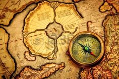 Vintage compass lies on an ancient map of the North Pole (also Hyperborea). Arctic continent on the Gerardus Mercator map of 1595.