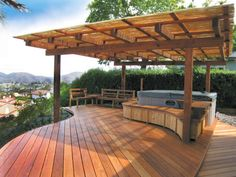 An arbor with a bamboo canopy allows guests to enjoy views from this exquisite Wood Shop Co. deck rain or shine.