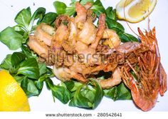 Fried #seafood of #shrimp and squid with #salad and  #lemon, typical italian food - stock photo