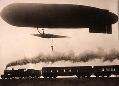 Stunts: a zeppelin flying low over a steam locomotive. Below the airship is a man on a rope. Place and date unknown.