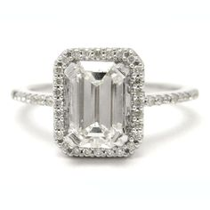 Engagement ring with a large emerald cut diamond set as a center stone, accented by a halo of diamonds.