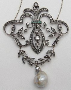 A stunning showpiece Victorian diamond baroque pendant necklace accented with emeralds and a natural pearl.