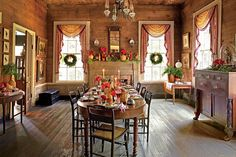 Cozy Christmas - Christmas in the Dining Room - Southernliving. This tablescape evokes rustic elegance. The deep wood tones of the floor and walls ground the room's design, and moments of decor—ruby-hued flowers, glowing candles, and pine garland greenery—keep the room feeling festive, lively, and ready for Christmas dinner.