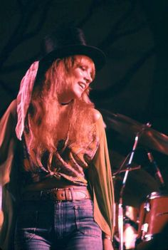 Stevie onstage wearing jeans, a knotted loose blouse, a shawl of sorts, a heavy belt and a top hat on her wild mane of hair, performing live with the other members of Fleetwood Mac in Johnstown, P.A. 1975, not long after she signed with the band on New Year's Eve, 1975 and became an overnight sensation ~ ☆♥❤♥☆ ~