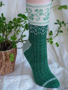 Yarn amounts: Adult medium (large) using a total of 285 (365) yards fingering weight yarn as follows: natural white 115(150) yards, green 170(215) yards. Shown in Lorna's Laces Shepherd Sock colors #0ns Natural and #20ns Pine.