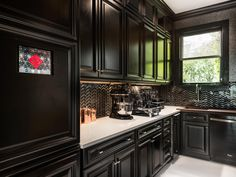 Geometric glass tiles add extra drama to the black, enamled cabinets in the San Francisco Decorator Showcase 2014 butler's pantry, designed by Steven Miller. The space features integrated storage and display to please the home chef.