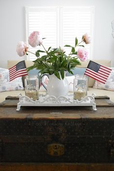 Create a simple Summer centerpiece. Start with a pitcher or vase (Homegoods has oodles) like this enamelware number. Add peonies, and flank with mason jars filled with sand, tealights and accented with flags! Perfect all season or as a Fourth of July highlight. foxhollowcottage.com