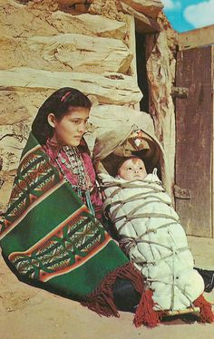 Indians - A Young Navaho Indian Mother with Papoose strapped onto its cradle board. The homes are hogans like the one that is in the background.