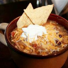 Chicken tortilla soup...i would add black beans and jalepenos.  To serve:  top with sour cream, diced avacado, and fried tortilla strips.  Made a soup similar to this, but not with corn and not in crock pot.  *GOOD!