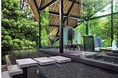 Indonesia Bali Ubud Lotus Villa Steps Across IInfinity Edge Reflection Pool Into Glass Enclosed Room With Thatched Roof Coming To A Point Above The