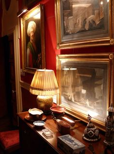 Red hallway, dimly light lamp with pleated shade, gold framed artwork, antiques