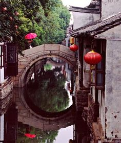 Ancient stone bridges built during the Ming Dynasty that arch over canals streaming from the Yangtze River Delta, auspicious red lanterns that sway in the wind, and temples with roof eaves that curve upward like wings. And the secret's out: towns like Zhouzhuang or Tongli