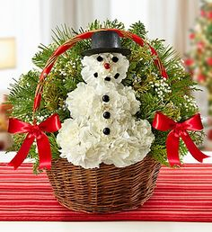 "Feelin' Frosty™ - handled willow basket accented with red ribbon is filled with assorted greens and a ""snowman"" made of fresh white carnations. $44.99"