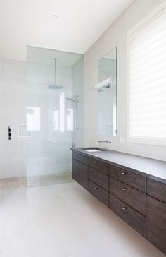 White bathrooms often feature glass showers for cohesiveness throughout
