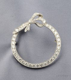 Art Deco Platinum and Diamond Circle Brooch, surmounted by a bow, set with old European and old single-cut diamonds, millegrain accents, dia. 1 3/8 in.