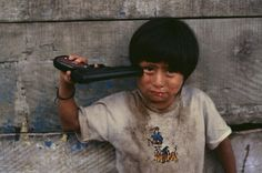 "Steve McCurry: ""I saw this young boy weeping on the side of the road in a village in a mountainous area of Peru. Some of the other children he was playing with were tormenting him. He had a toy gun in his hand, I walked over to see if I could help, but the child wasn't able to respond because he was so upset. He walked away towards his house."""