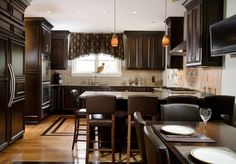 The Howland Group remodeled this Hyde Park kitchen for a busy family. With lots of custom details like the fleur-de-lis backsplash, this kitchen is stylish and functional. Dark cabinets, light granite countertops, light hardwood floors with a custom inlay, refrigerator with matching custom panels and stainless steal appliances updated this kitchen to fit the family's design style.  Photos by Gomsak Photography Dark Panels, Light Granite Countertops, Light Hardwood Floors, Kitchen Remodel, Granite Countertops, Interior, Countertops, Home Decor, Stainless Steal Appliances