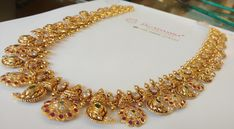 Stunning gold necklace with mango and flower hangings. Necklace studded with rubies and emeralds. Choker Jewelry, Gold Jewellery, Pendant Jewelry, Diamond Jewelry, Jewelery, Gold Necklaces, Half Saree, Emeralds, Necklace Designs