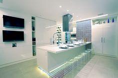 Azulejos artesanais cobrem uma faixa contínua do piso de porcelanato à parede na cozinha / Murad + Estrela Arquitetura
