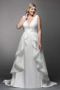 Clarabelle is a sweet A-line gown with a V-neckline and soft tulle cape on the skirt. The cape is edged with lace embroidery and falls in beautiful ruffles down the front. The top features lace embroidery traveling up the front and onto the back.
