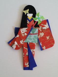 A Japanese paper doll, wearing Kimono (traditional clothes) and carrying a paper pinwheel, and have hair decoration. Made by high quality Japanese
